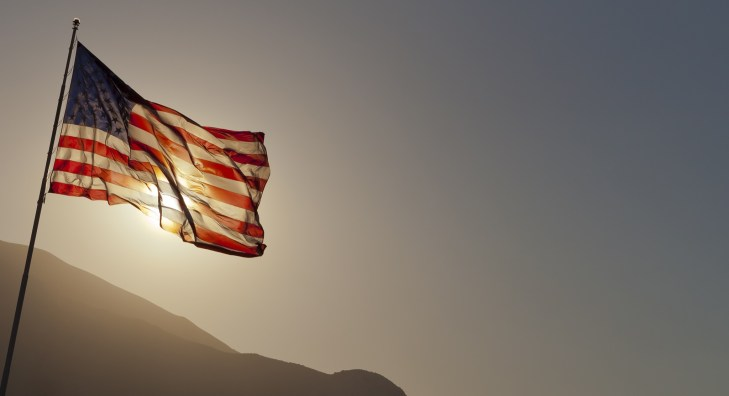 Back-lit American flag flying on pole with copy space