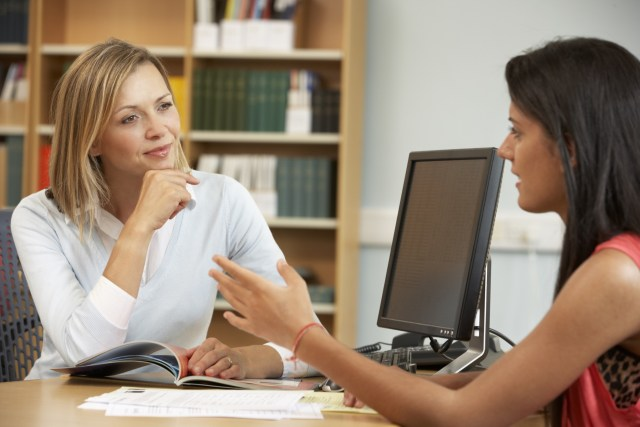 Professor mentoring student: college tutor with student