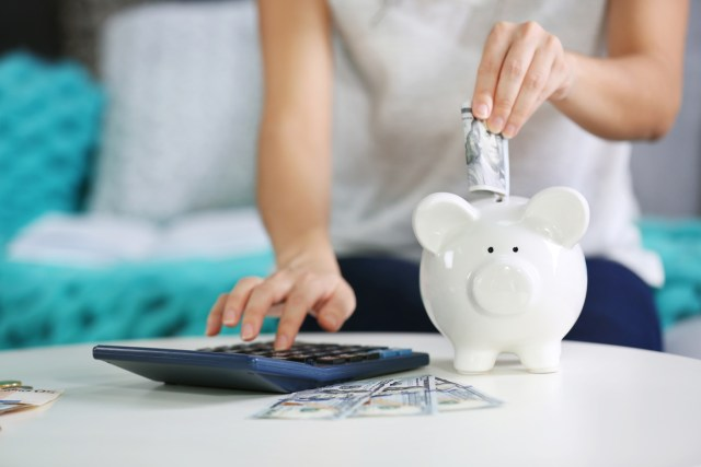 Female hand putting money into piggy bank and counting on calculator closeup