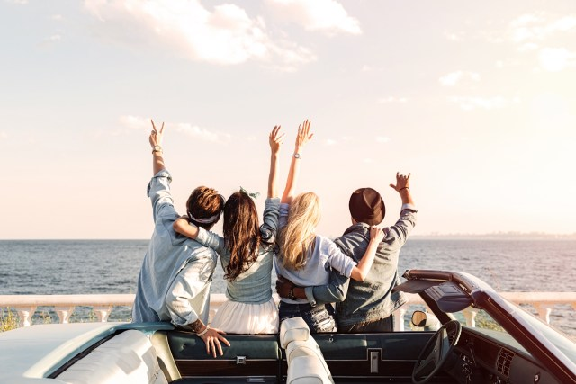 Road trip; Back view of happy young friends standing with raised hands near the car