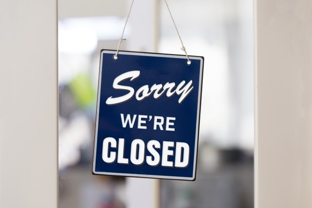 """"""" Sorry we're closed """" sign in blue and white, on shop glass door with white panels."""