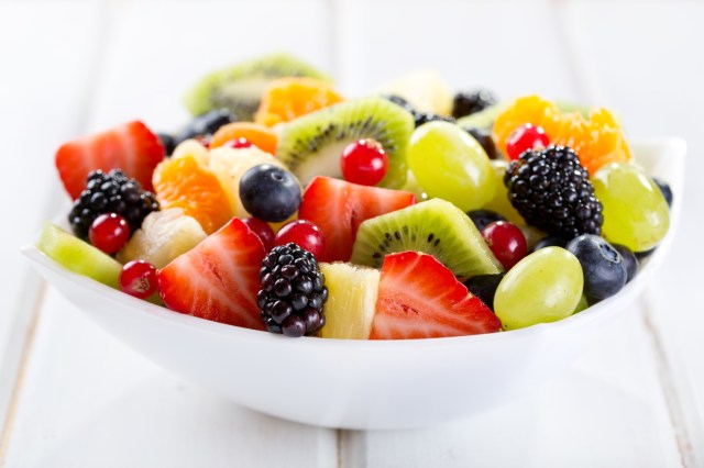 A bowl of healthy, sliced fruits.