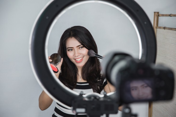 Beauty vlogger doing a tutorial in front of a camera and ring light