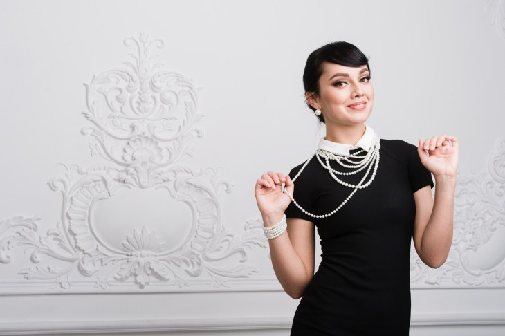 Woman wearing a black dress with a white collar and pearls