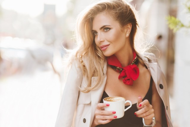 Woman wearing red neckerchief with black dress and tan trench coat enjoying coffee