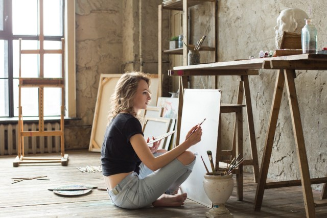 Girl sitting on the floor of an art studio in front of a blank canvas