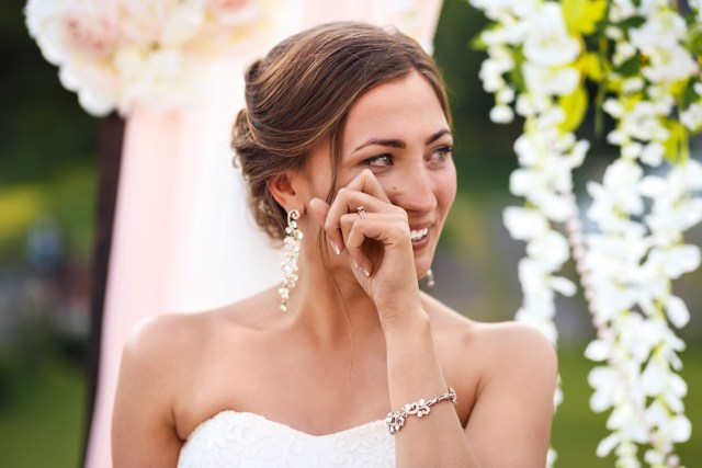 A beautiful, brunette bride, crying tears of joy on her wedding day.