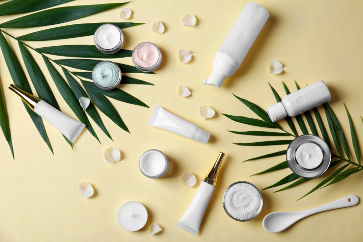 Skincare products displayed on a table with leaves