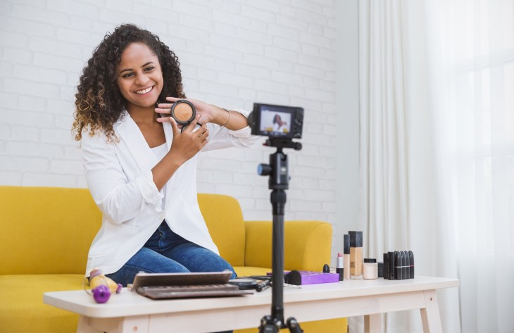 Woman filming a makeup tutorial in front of a camera