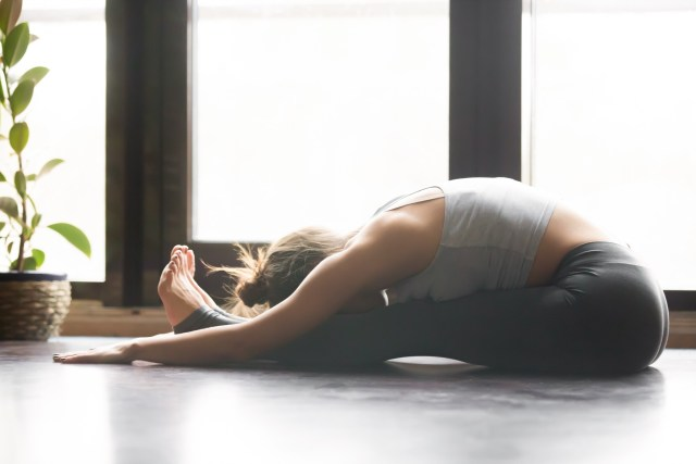 Woman practicing seated forward bend in her home