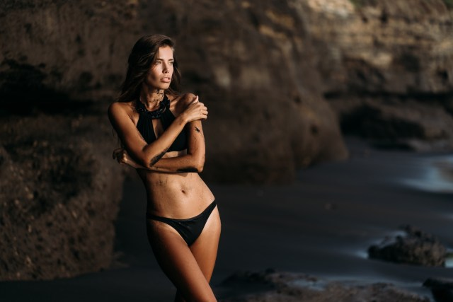 Woman wearing black swimsuit with halter neck top