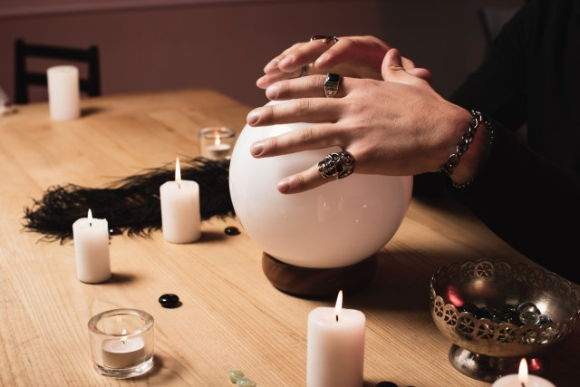 Bejeweled hand covering crystal ball