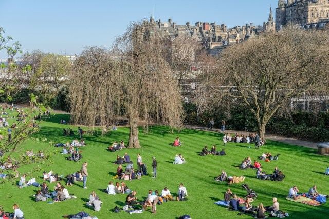 Edinburgh, United Kingdom. 8 April 2017 : People sitting, laying and relaxing in Princes Street Gardens, the public space in city center of Edinburgh.
