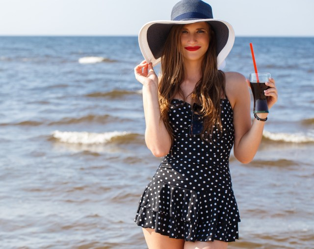 Woman wearing polka-dotted swimsuit with a skirted bottom