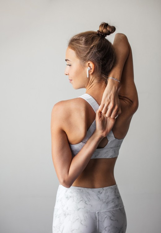 Woman in all white workout gear wearing top knot while stretching
