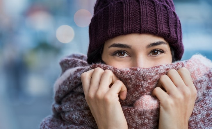 Winter portrait of young beautiful woman covering face with woolen scarf