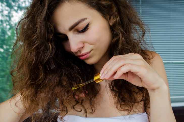 Young beautiful curly woman uses yellow serum for hair.