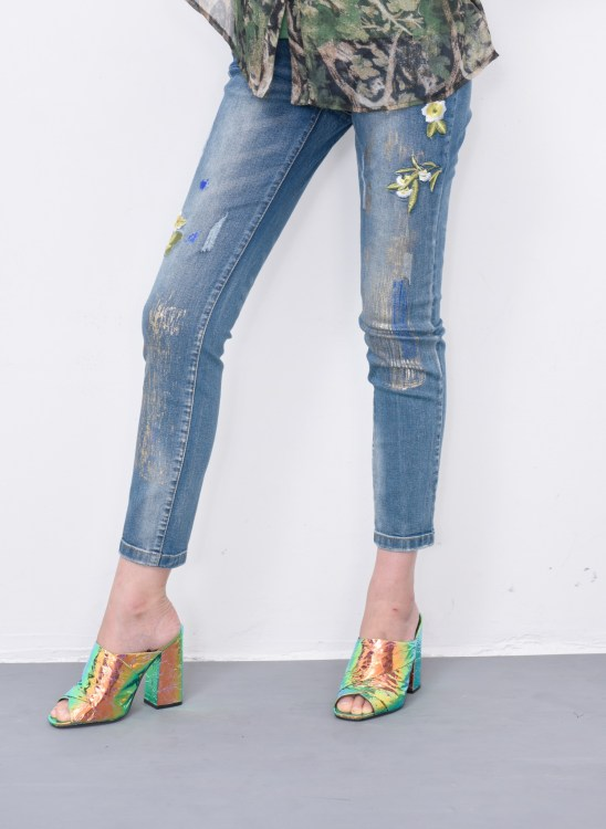 Woman's legs in embroidered flower jeans and green high hell shoes posing in studio