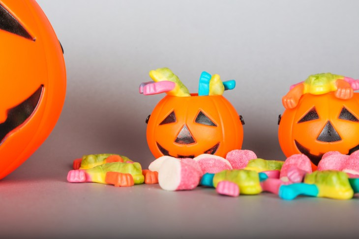 Happy Halloween Trick or Treat jack-o-lantern buckets and pile of colorful sweets candy on gray background. Plastic pumpkins to collect candy