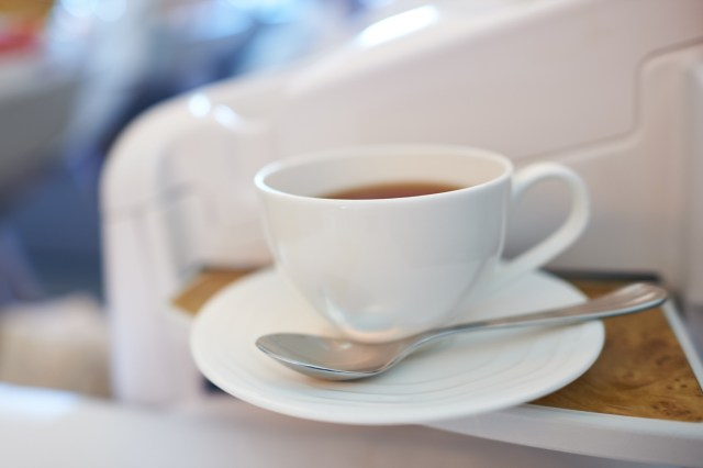 White cup with hot tea served at business class of modern airplane