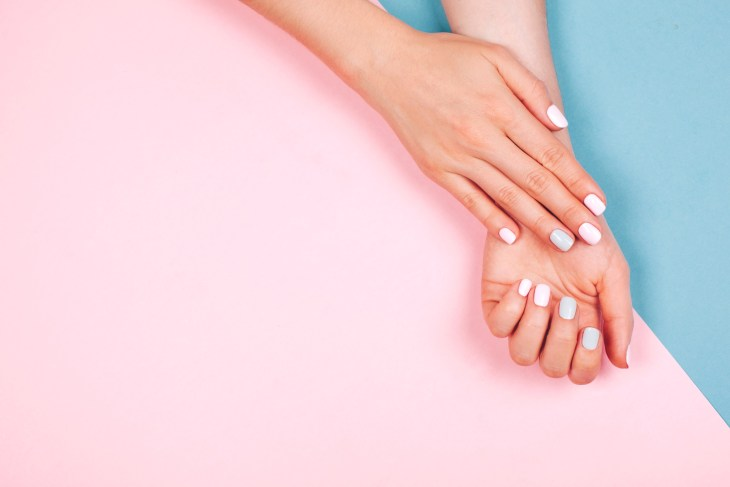 Beautiful young woman's hands on pink and blue background