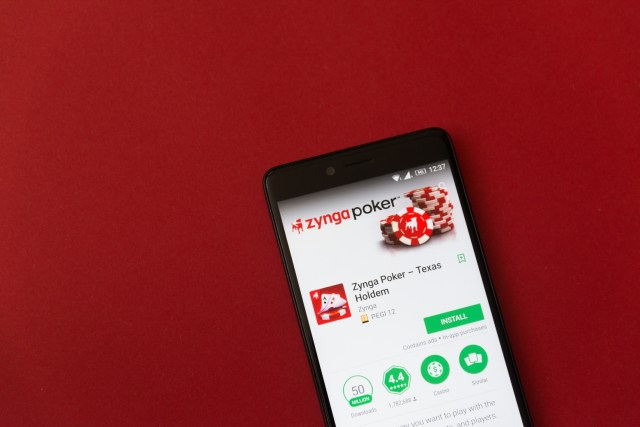 Smartphone with Zynga poker game application in google play store on red background
