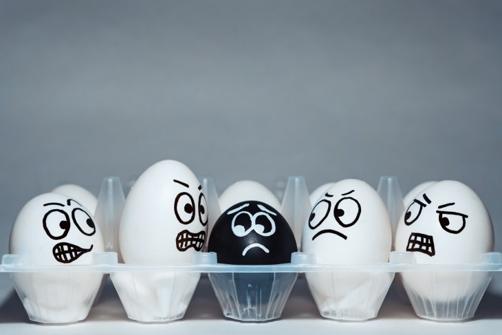 white eggs with angry faces looking at black egg scared in a plastic cart against grey background
