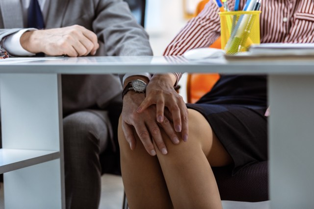 Hand on the knee. Shameless man harassing his expressive workmate while touching bare legs under table surface