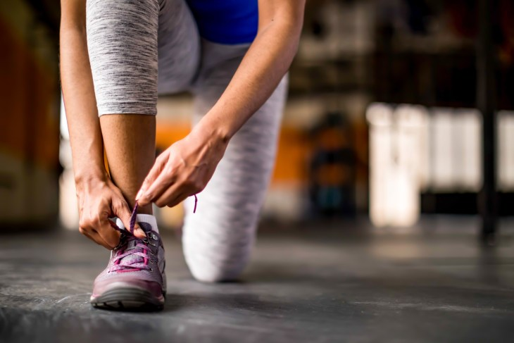 Woman tying her shoe in an open empty gym