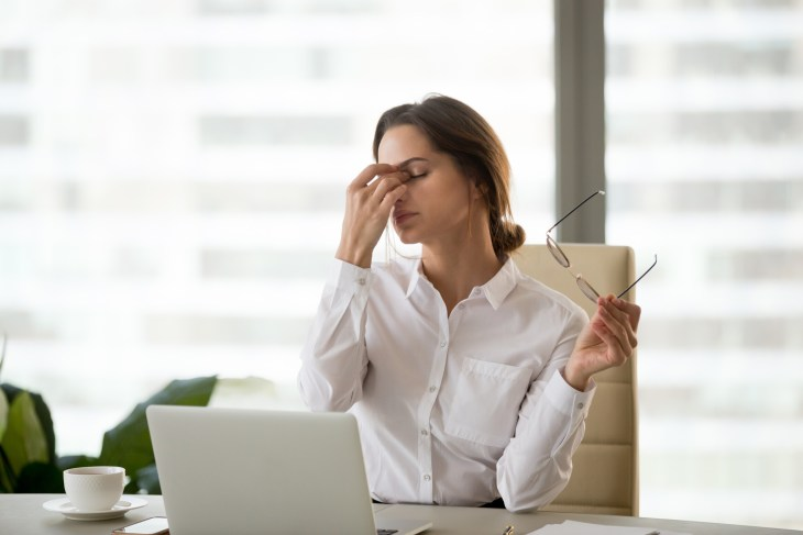 Fatigued businesswoman taking off glasses