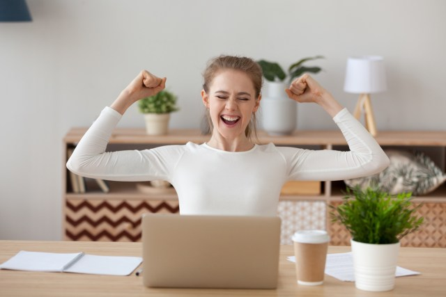 Happy woman sitting at the desk opposite laptop