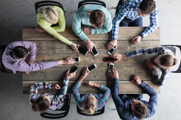 Team of people put smartphones to table
