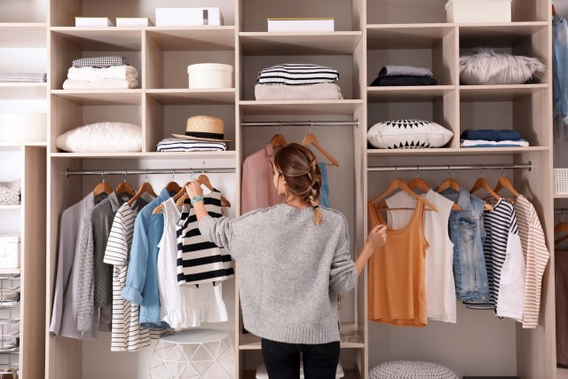 Woman choosing outfit from large wardrobe