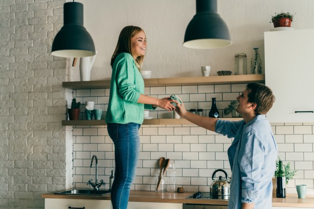Young happy couple giving each other cup from shelf