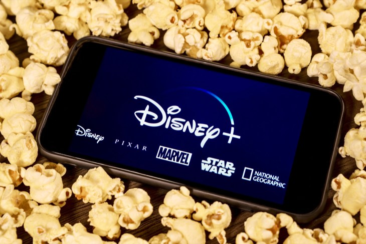 Grand Prairie, TX/USA - Aug 2019: Disney Plus on smartphone with popcorn. Dinsey+ is a new streaming subscription service that will feature Marvel, Pixar, Star Wars, and National Geographic content - Image