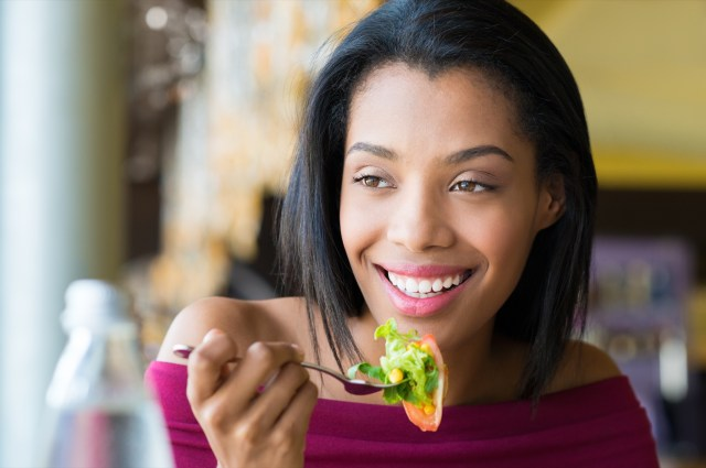 Young woman eating fresh salad