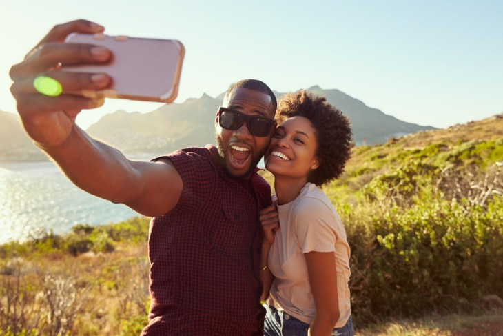 Young Couple Pose For Holiday Selfie On Clifftop.