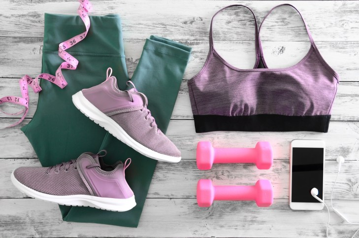 Gym clothes against wood floor: lilac colored sports bra and sneakers, forest green leggings, pink dumbbells, iPhone with earphones and pink measuring tape.