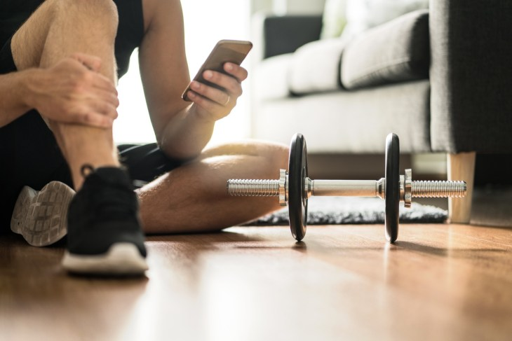 Man in athletic attire sitting on the floor holding phone during at-home workout.