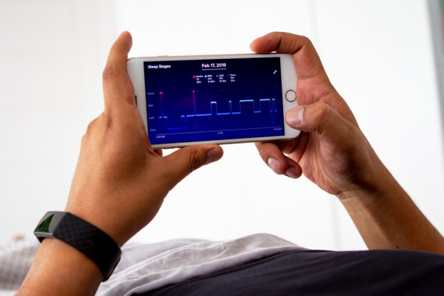 Man holding iPhone with Sleep Cycle app.