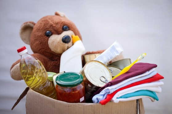 Box filled with stuffed bear, clothes, canned and bottled food and personal hygiene items.