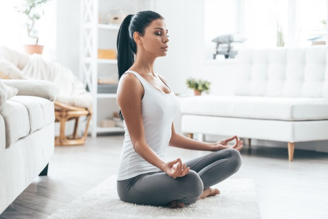 young woman exercising and sitting in yoga lotus position while resting at home
