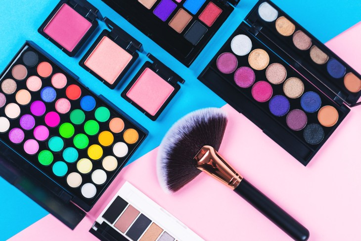 Makeup and beauty products on pink and blue background. Eye shadow palettes. fan contouring brush and blushes.