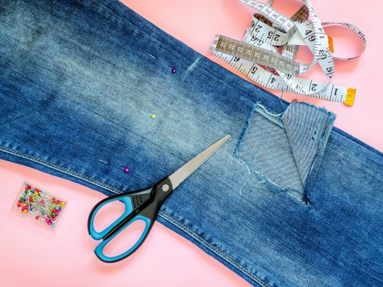 Folded in a half blue jeans with large hole on pant leg below the knee, multi coloured headed sewing pins, white tailor tape with centimeters and inches and scissors on a pink background