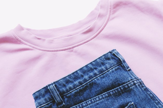 Light pink sweatshirt and blue jeans. Flat lay women clothes, simple style, trendy outfit