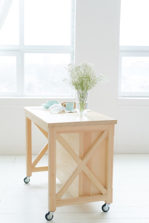 A wheeled kitchen island with a flower vase on top.