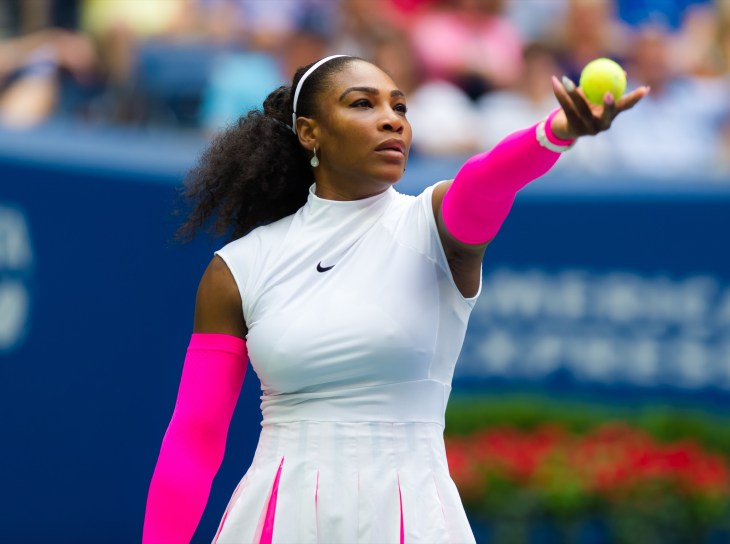 Serena Williams On Tennis Court Serving Ball In Pink And White Dress