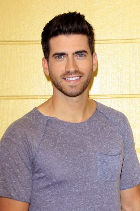 Photo of Ryan Rottman in front of yellow background with grey t shirt on.
