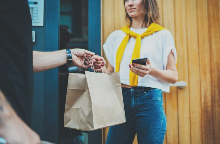 A man delivering a brown bag to a woman.