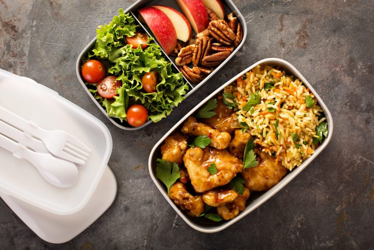 A to go bento box broken down with a salad in the one container and rice and chicken in the other.